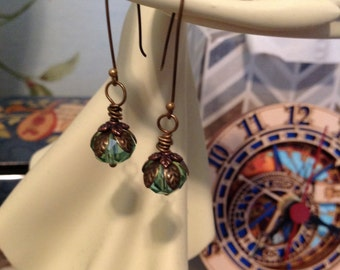 Green glass bead dangle earrings with brass leaf/floral findings detail