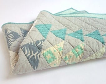 Baby quilt with modern, fresh design. White, minty green and teal triangles on a grey background.