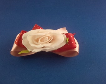 Hair comb decorated with red and pink bows plus pink flower