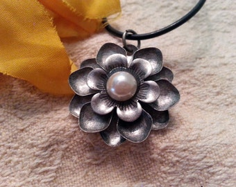 Antique Silver flower with pearly center pendant on a black cord necklace