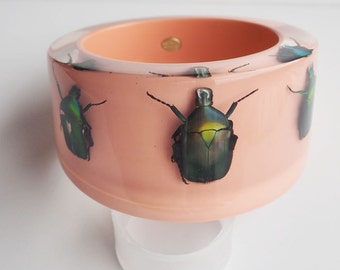 Large soft pink lucite bangle with real metallic beetles