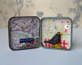 Artwork in vintage tin - mixed media - Blackbird in embroidered garden