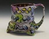 Whimsical mug with purple lime green blue and yellow design