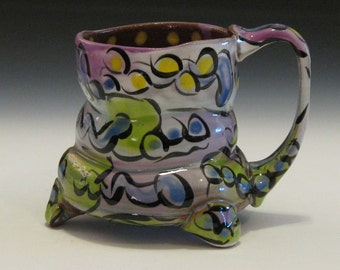 Whimsical mug with purple lime green blue and yellow design
