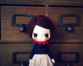 Little short hair doll with red dot skirt.