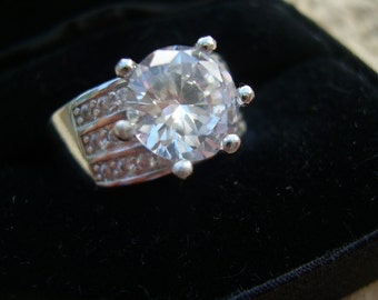 Beautiful S925 Sterling silver and unidentified Clear Gemstone set in six (6) prong setting, band ring Size 8-8.25