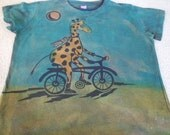 Adorable giraffe riding her/his bicycle, woman's large discharged and dyed t-shirt, procion dyes, turquoise, orange, yellow, greens