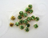 4mm Green Glass Sew on Rhinestones. Gold Colored Settings. QTY: 50 Pieces.