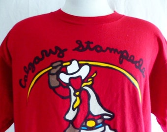 vintage 80's 90's Marc Tetro Calgary Stampede Canada blood red graphic t-shirt bright primary color cowboy print travel tourist souvenir XL
