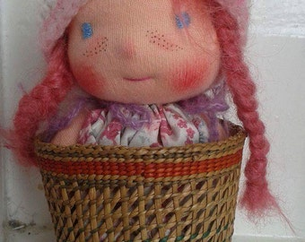 Milla is a Waldorf pocket doll in a little basket.