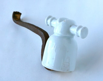 Old ceramic electricity insulator on metal arm