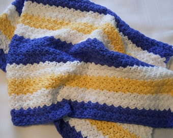 Baby blanket, crocheted in a soft white, blue and yellow color.