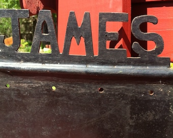 A Black Heavy Sign/Plaque With The Cut-Out Name Of James