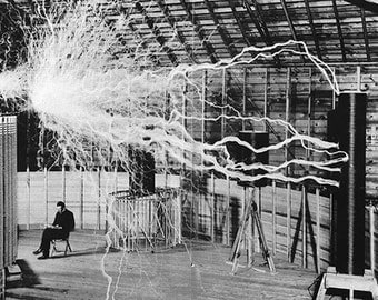 Nikola Tesla in his lab, casually reading while volts of electricity fly through the air, 1899.. Photo Print