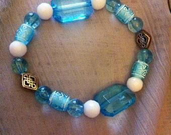 Light aqua and white stretch bracelet with Celtic knot beads.