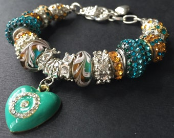 Teal and amber crystal bead bracelet with dangling heart charm.