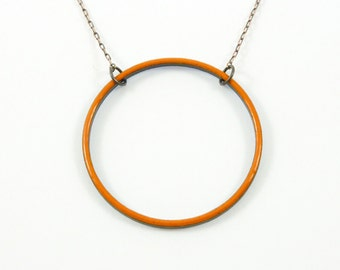 Handmade reversible enameled necklace; orange/periwinkle circle with adjustable chain.