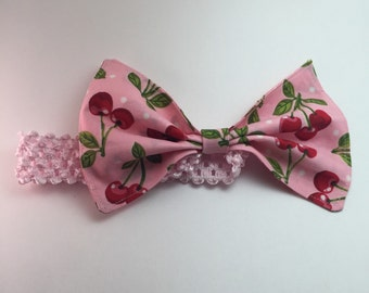 Newborn pink cherries stretchy headband with large bow.