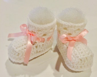 Handmade crocheted white baby booties with pink ribbon. Free shipping in the USA