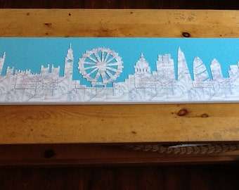 The London Skyline finely cut out of real London Underground tube maps on a coloured background, on a box canvas.