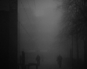 A Dark Commute. A dark, eerie monochromatic fine art photographic print of figures moving through fog on a freezing winters morning.