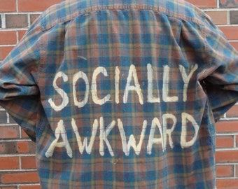 SOCIALLY AWKWARD bleached onto the back of a repurposed multi-color flannel shirt