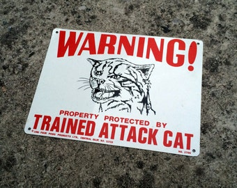 Warning! -- Novelty sign exaggerating the ferocity of a domestic cat -- Four Paws Products Ltd.