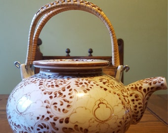 Ceramic teapot, wicker handle,made in Vietnam.