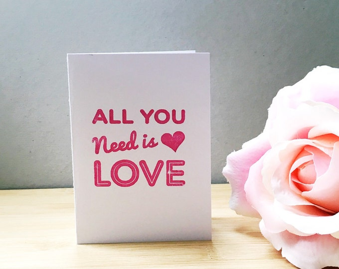 Pink hand printed 'All you need is love' typographic mini greetings card