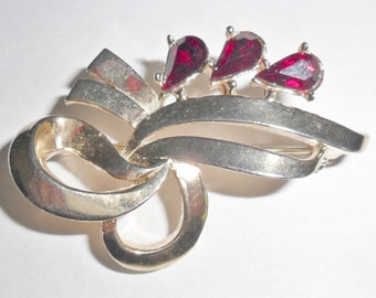 Pretty vintage goldtone abstract ribbon brooch with red rhinestone accents