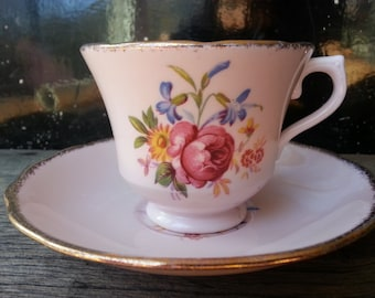 Vintage Vale footed tea cup and saucer in pretty pink with a thick gold trim and floral motif from late 1940's