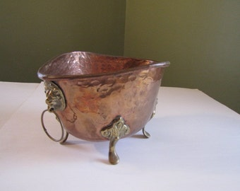 Copper planter with brass legs, and lion heads