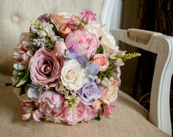Pastel silk wedding bouquet in pink, ivory and lilac. Made with artificial roses, peonies, hydrangea, brunia and assorted greenery.