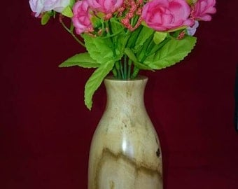 Bud vase with artificial flowers and a plastic tube for fresh flowers