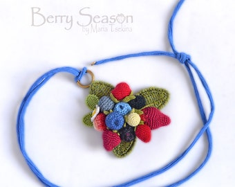 Crochet berry pendant on a blue cord