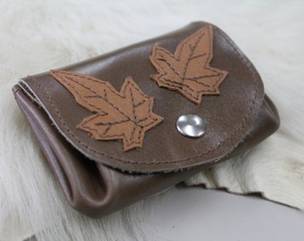 wallet brown leather smooth and slightly shiny, decorated with leather leaves