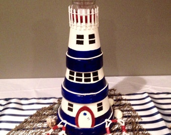 Lighthouse made from terracotta pots for decor or nautical party centerpiece.