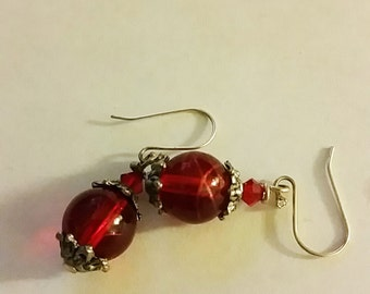 Ear rings with silver hooks, silver-colored decorations and red glass beads