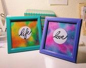 Dos cuadros galácticos con las palabras Love y Life