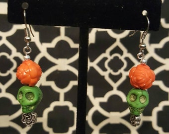 Day of the Dead, DOTD, handmade drop earrings. Green skull with an orange flower. Beaded. Howlite skull.