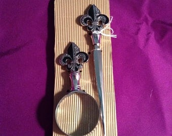 Silver and black magnifying glass and letter opener with fluer de lis