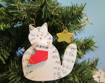 white cat ornament with christmas stocking and star