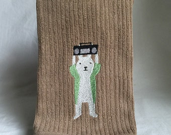 "Embroidered bunny with boombox recalling the movie ""say anything"" on brown vertical bar towel"