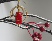 Splashes of metallic gold accent the rectangular red beads dropping from these gold hoops