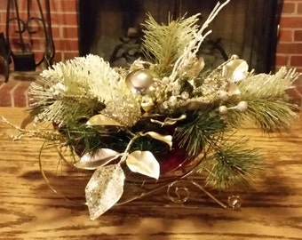 Sleigh with gold, white and pine arrangement