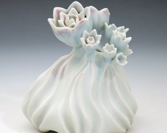Carved porcelain sculpture, with flowers in pastel blue, green and peach with pink blush