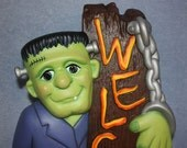 Handpainted Ceramic Frankenstein Holding a Log that says Welcome Halloween Decoration