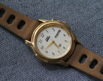 Vintage Timex watch with gold tone case and tan vintage rally strap