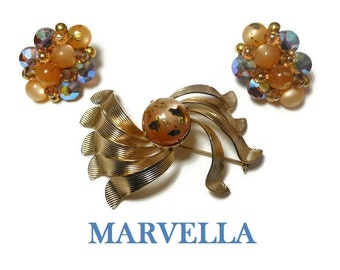 Marvella 1950s brooch and earrings set, a gold ribbons with gold splattered glass bead center, clip earrings have aurora borealis beads AB