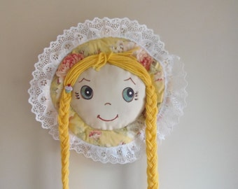 Barrette Holder bluish green eyes yellow hair yellow bonnet with pink flowers with cupcake accent